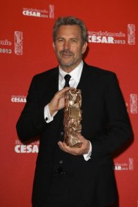 """I promise not to cry!"" An emotional Kevin Costner cradles his prize."