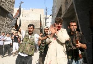 Spot the Bad Guy: Syrian rebels with bloodied captured policeman in Aleppo