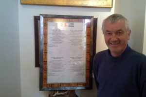 """I wouldn't have thought of driving in France 10 years ago but it's second nature to me now."" Dunmanway-Quéven Twinning treasurer Stephen Daly stands before the framed signed twinning charter"